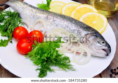 trout with lemon and fresh vegetables  - stock photo