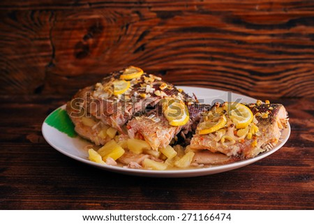 Trout with pineapple potatoes. Cook cuts the fish on a plate. Cooked trout, roasted in the oven. Fish with lemon, pineapple, potatoes. - stock photo