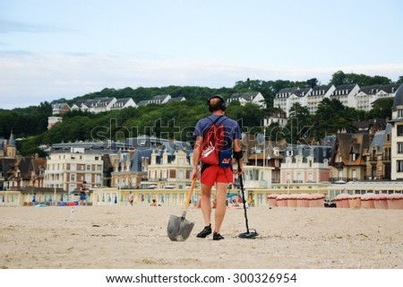 TROUVILLE-SUR-MER, FRANCE - JULY 10, 2015: Man searching for the treasure (jewelry, coins and other valuable metal items that were lost in the beach's sand during the day) using a metal detector. - stock photo