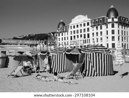 TROUVILLE-SUR-MER, FRANCE - JULY 10, 2015: People relax on the beach. Trouville-sur-Mer and nearby Deauville are popular summer resorts in Normandy region. - stock photo