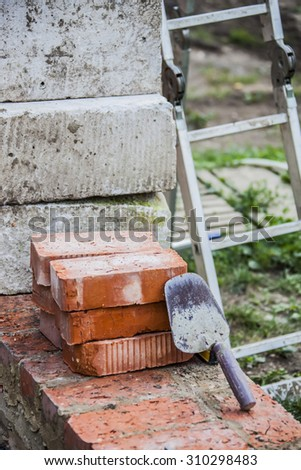 trowel and bricks lying on the basement of an unfinished house, building behind the stairs