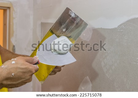 trowel full of plaster, skim coating a wall - stock photo