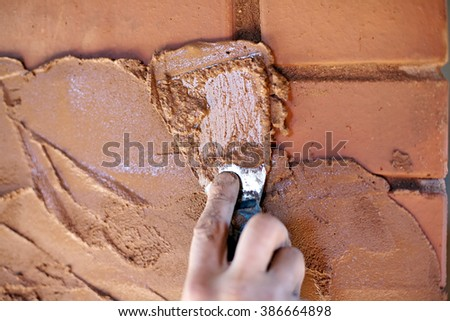 trowel in worker hand closeup on red brick wall background - stock photo
