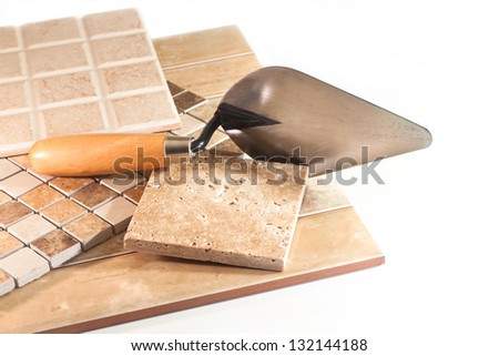 Trowel, marble and ceramic tiles on white background - stock photo