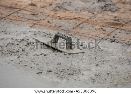 trowel on a newly poured concrete floor