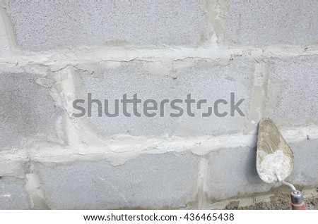 Trowel on cinderblock gray background. against the background of the brickwork is trowel - stock photo