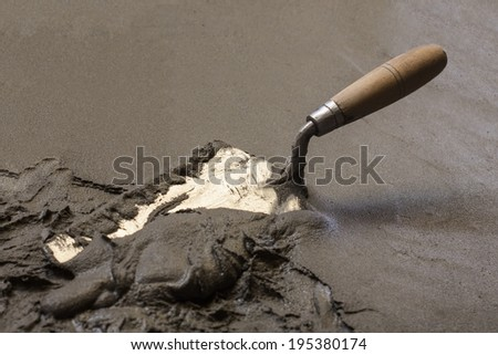 trowel  with wet concrete floor, construction tools - stock photo