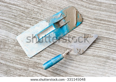 Trowels and other masonry tools on an unfinished concrete floor background - stock photo