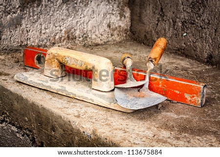 Trowels and other masonry tools on an unfinished concrete wall background - stock photo