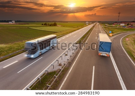 Truck and bus driving in motion blur on the freeway towards the setting sun. Rush hour on the motorway near Belgrade - Serbia. - stock photo
