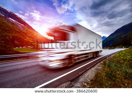 Truck and highway at sunset. Truck Car in motion blur. - stock photo