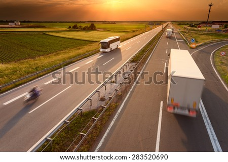 Truck,  bus and motorcycle driving in motion blur on the freeway towards the setting sun. Rush hour on the highway near Belgrade - Serbia. - stock photo