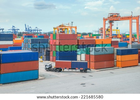 Truck carries container to a warehouse in dock - stock photo