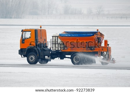 Truck deicing a road in winter - stock photo