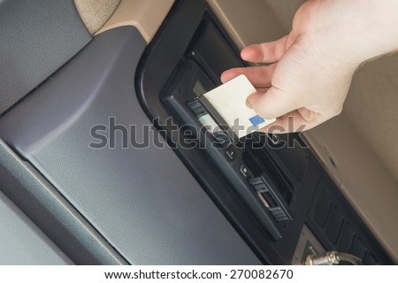 Truck driver is inserting tachograph card to the device inside the truck cab. - stock photo
