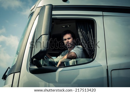 Truck driver sitting in cab - stock photo