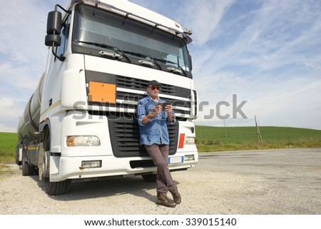 Truck driver working with smartphone - stock photo