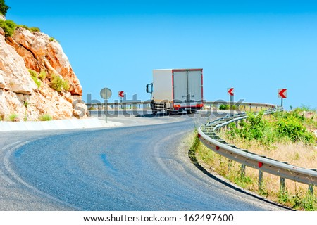 truck driving on a mountain road on a sunny day - stock photo