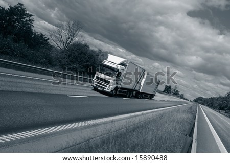 truck driving on highway, slightly tilted perspective and in a bluish toning concept - stock photo