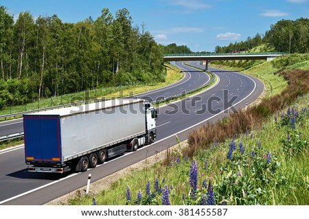 Truck driving on the highway with a double bend in a landscape. The bridge over the highway. Deciduous forest along the highway. View from above. Sunny summer day with blue skies and white clouds.