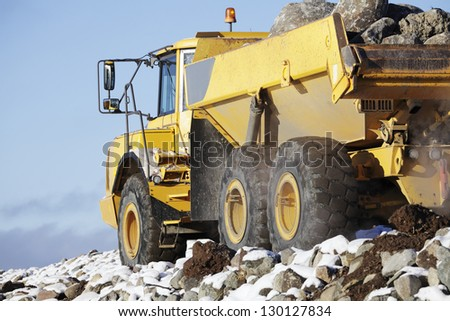 truck driving, snow and rocks, close-ups view