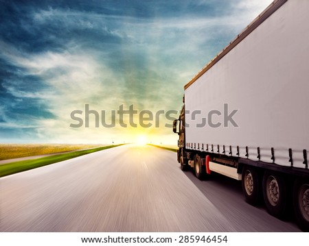 Truck driving towards sunset - stock photo