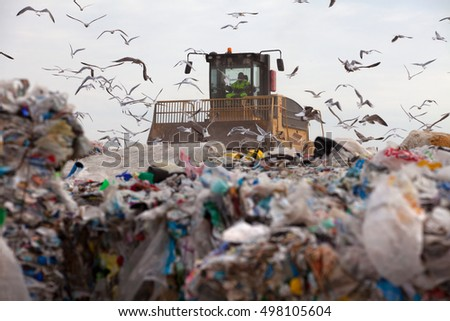 Truck flattening household garbage on a landfill waste site