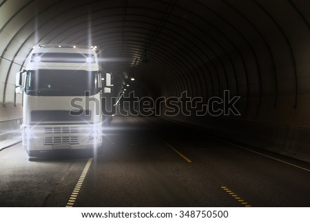 Truck in a long road tunnel - stock photo