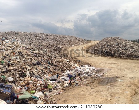 truck is dumping the gabage from municipal. The open dumping land fill with scaventure and machine. - stock photo