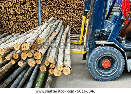 truck loading pile of wood in logs storage for construction or industrial work - stock photo