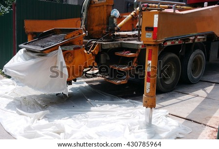 Truck-mounted concrete pump. The optimized hopper shape reduces concrete settlement and residual concrete. The hopper is easy to clean. White plastic sheets prevent stains on road and side of hopper. - stock photo