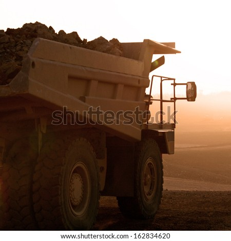 truck on a construction site in sunset - stock photo