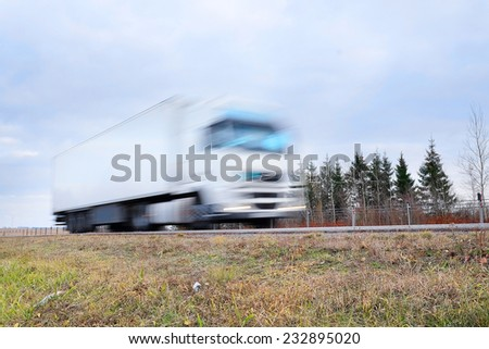 Truck on a highway. Truck is blurred because of movement - stock photo