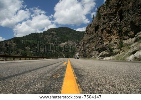 Truck on mountain lonely road - stock photo