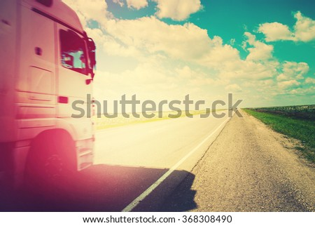 Truck on Road with Summer Landscape. Transportation Far Distances - stock photo