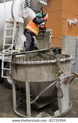 Truck operator pouring cement into crane bucket - stock photo
