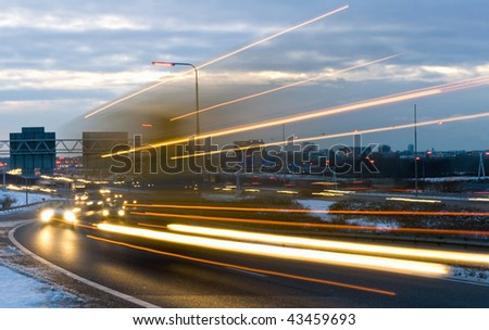 Truck passing by on a motorway junction on a winter evening - stock photo
