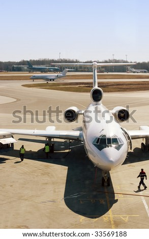 Truck refueling an airplane on the airport - stock photo
