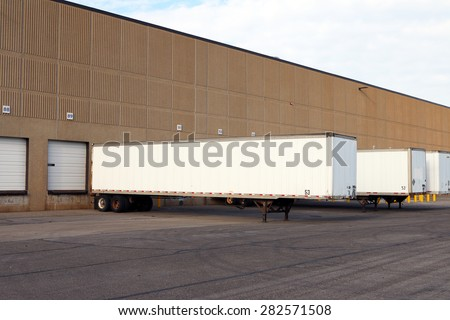 Truck semi trailers waiting to be unloaded at a warehouse or factory.   - stock photo
