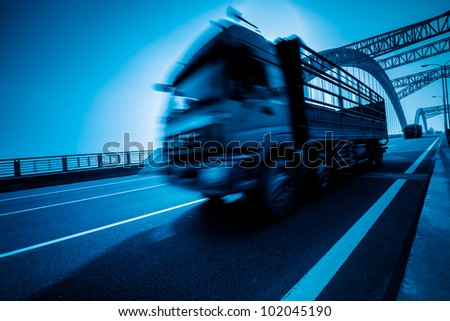 truck speeding through a bridge of ciy,blue toned. - stock photo