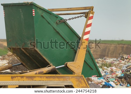 Truck tipping garbage from container on junk yard  - stock photo