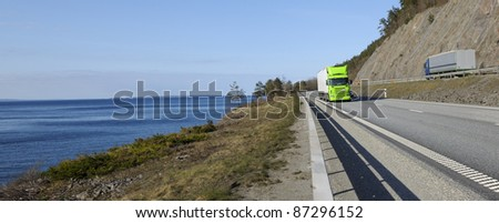 truck transports, driving on scenic route of highway, panoramic view. - stock photo