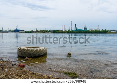 Truck tyre in the mud polluting the land - stock photo