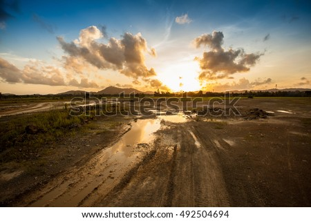 truck wheel mark ground with field and sunset cloudy sky
