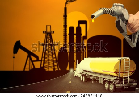 Truck with fuel tank on the highway into oil rig and hand holding a classic fuel nozzle pumping with beautiful sunset sky in concept of industrial petrochem