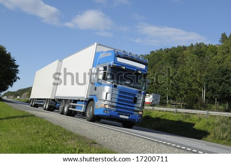 trucking on scenic freeway, tilted perspective, trademarks removed. - stock photo