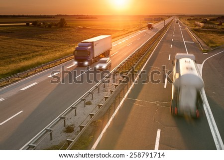 Trucks and car in motion blur on the freeway towards the setting sun. Rush hour on the motorway near Belgrade - Serbia. - stock photo