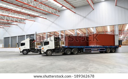 trucks at loading dock shipping industry warehouse - stock photo