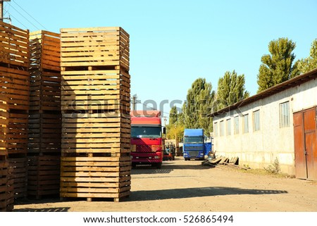 Trucks beside empty wooden crates for harvesting