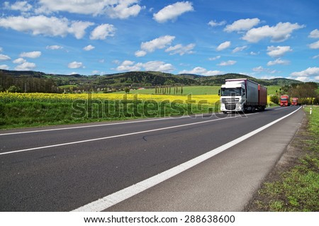 Trucks driving on the asphalt road around the yellow flowering rapeseed field in rural landscape. Wooded mountains in the background. Blue sky with white clouds. - stock photo